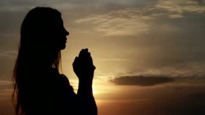 stock-footage-prayer-woman-with-hands-folded-at-seaside-during-sunset