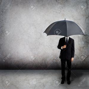 12044949-Business-man-holding-an-umbrella--Stock-Photo